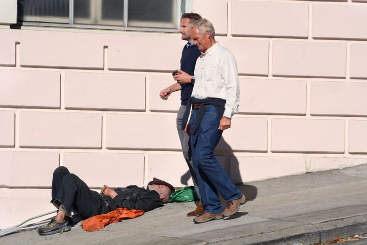 Two men walk past a homeless man sleeping on a sidewalk in San Francisco, California, Sept. 16, 2018.