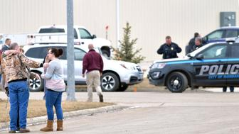 Family and friends console each other at the scene near the south side of the RJR Maintenance and Management building in Mandan, N.D., Monday, April 1, 2019. (Mike McCleary/The Bismarck Tribune via AP)