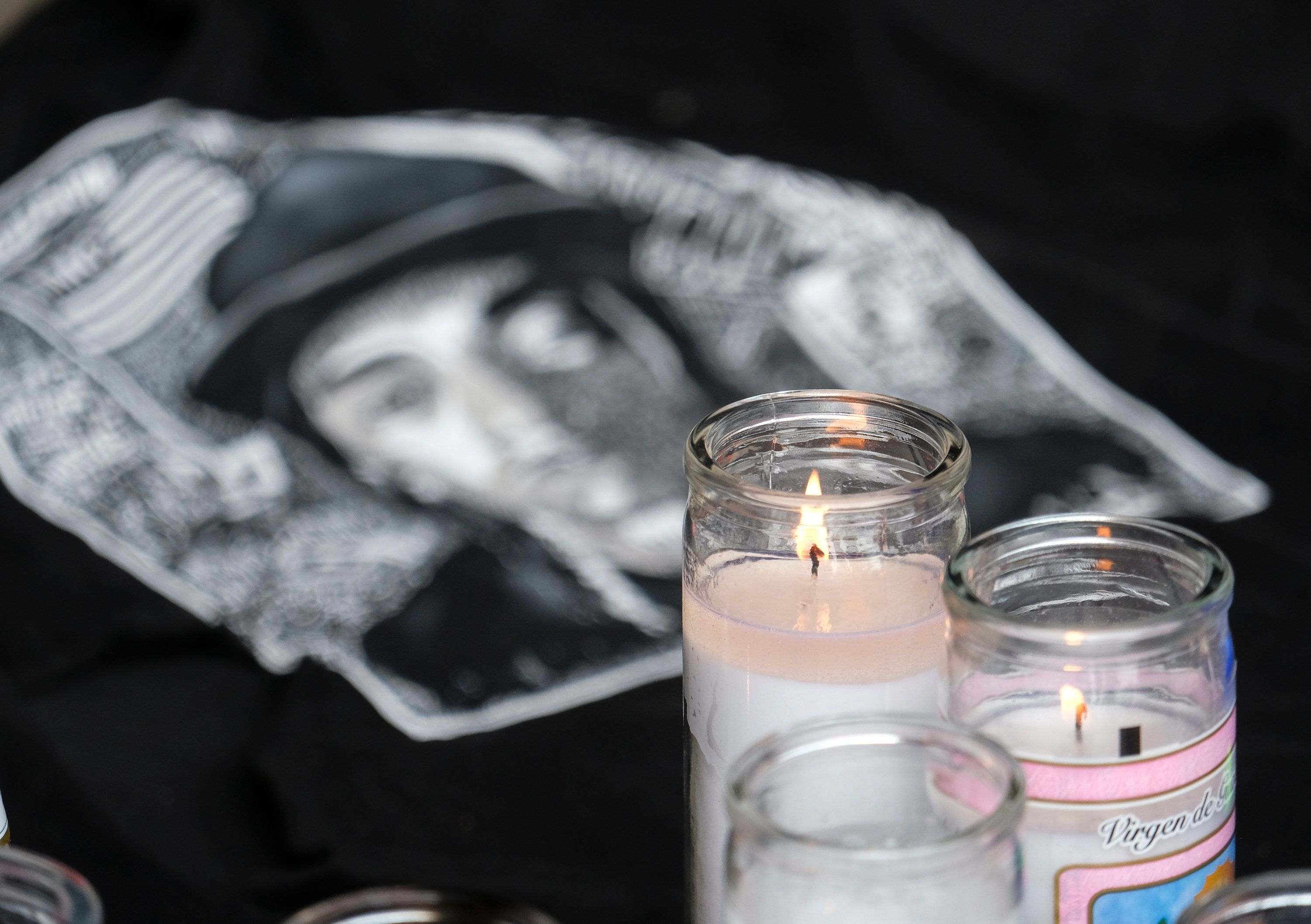 Candles appear at a makeshift memorial for rapper Nipsey Hussle in the parking lot of his Marathon Clothing store in Los Angeles, Monday, April 1, 2019. Hussle was killed in a shooting outside the store on Sunday. (AP Photo/Ringo H.W. Chiu)