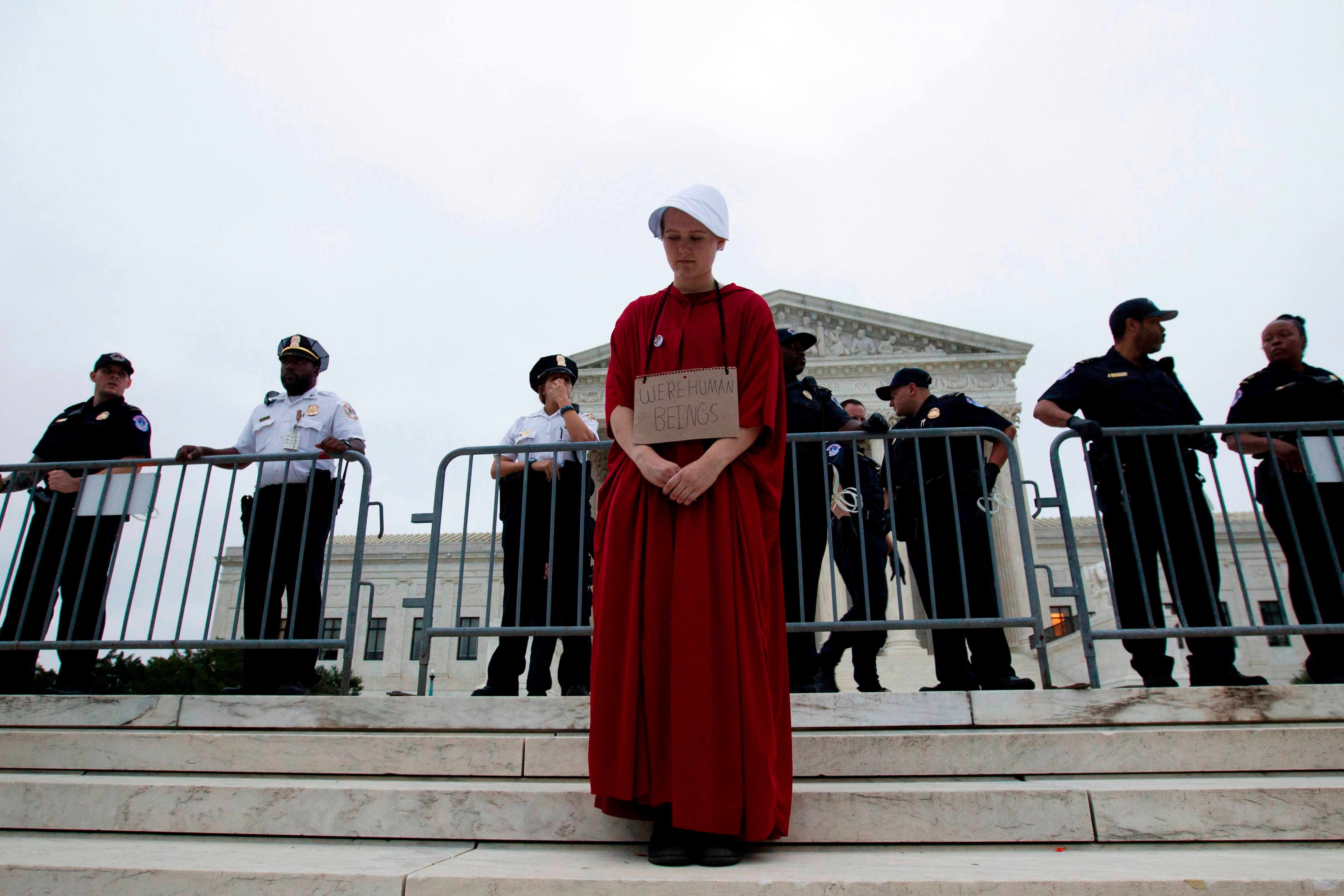 TOPSHOT - Payton Sander wearing a dress from The Handmaid's Tale protests at the steps of the US Supreme Court to protest against the appointment of Supreme Court nominee Brett Kavanaugh in Washington DC, on October 6, 2018. (Photo by Jose Luis Magana / AFP)        (Photo credit should read JOSE LUIS MAGANA/AFP/Getty Images)