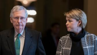 Senate Majority Leader Mitch McConnell, R-Ky., joined at right by aide Stefanie Hagar Muchow, walks to the chamber as the Republican-run Senate rejects President Donald Trump's declaration of a national emergency at the southwest border, at the Capitol in Washington, Thursday, March 14, 2019. The Senate voted 59-41 to cancel Trump's February proclamation of a border emergency, which he invoked to spend $3.6 billion more for border barriers than Congress had approved. (AP Photo/J. Scott Applewhite)