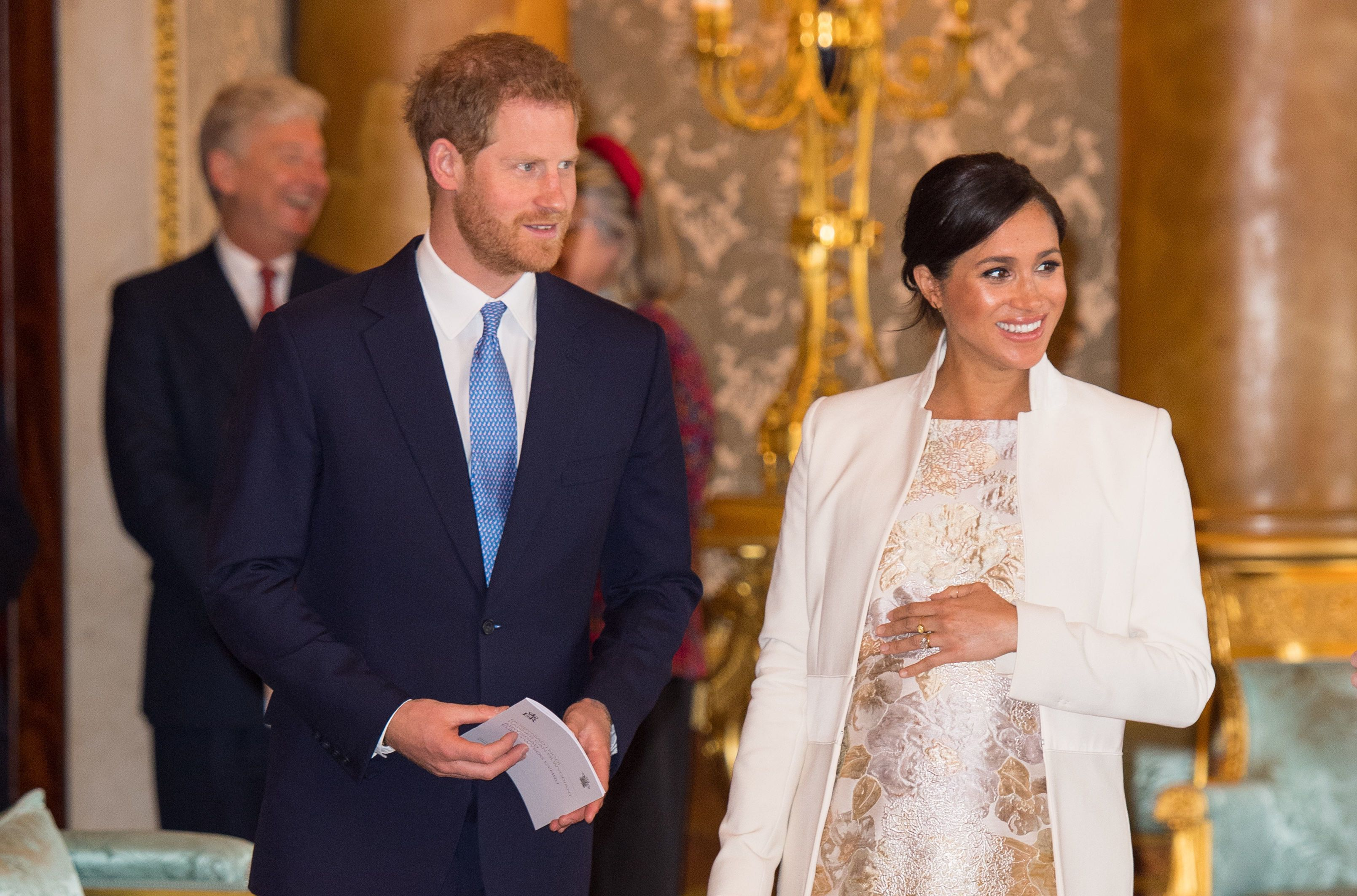 TOPSHOT - Britain's Prince Harry, Duke of Sussex, (L) and Britain's Meghan, Duchess of Sussex (R) attend a reception to mark the 50th Anniversary of the investiture of The Prince of Wales at Buckingham Palace in London on March 5, 2019. - The Queen hosted a reception to mark the Fiftieth Anniversary of the investiture of Britain's Prince Charles, her son, as the Prince of Wales. Prince Charles was created The Prince of Wales aged 9 on July 26th 1958 and was formally invested with the title by Her Majesty The Queen on July 1st 1969 at Caernarfon Castle. (Photo by Dominic Lipinski / POOL / AFP)        (Photo credit should read DOMINIC LIPINSKI/AFP/Getty Images)