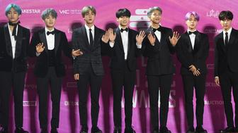In this picture taken on January 15, 2019, South Korean boy band BTS, also known as the Bangtan Boys, pose on the red carpet at the 28th Seoul Music Awards in Seoul. - The K-pop phenomenon BTS is estimated to generate nearly 4 billion USD a year for the South Korean economy, but the boyband's seven members will still have to perform nearly two years of military service, in contrast to the likes of Tottenham Hotspurs striker Son Heung-min who had been granted a controversial exemption. (Photo by Jung Yeon-je / AFP) / TO GO WITH AFP STORY  SKOREA-DEFENCE-SOCIAL-ENTERTAINMENT,FOCUS BY KANG JIN-KYU        (Photo credit should read JUNG YEON-JE/AFP/Getty Images)