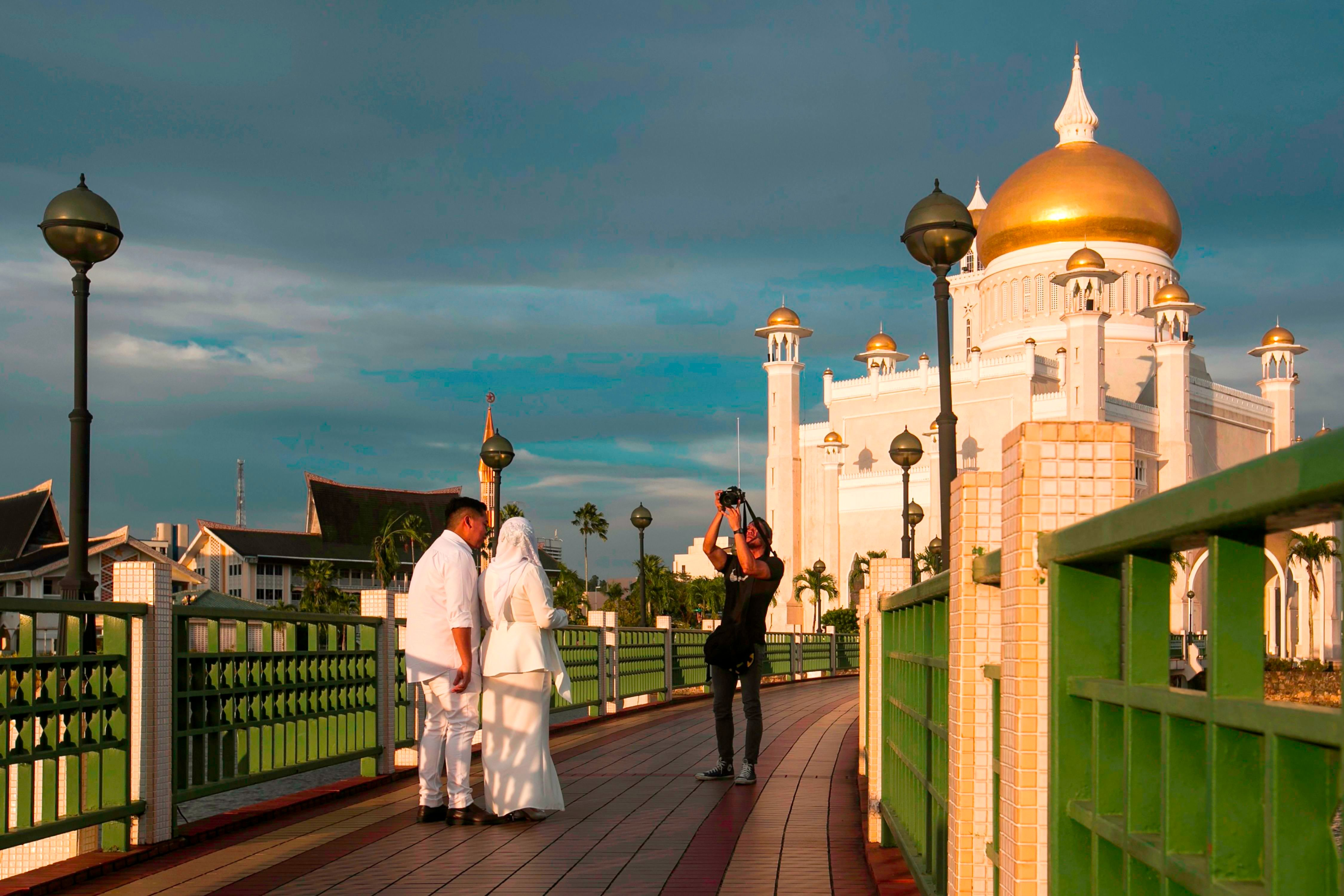 TOPSHOT - In this picture taken on April 1, 2019 a newlywed couple has their photographs taken at the Sultan Omar Ali Saifuddien mosque in Bandar Seri Begawan. - The United Nations decried on April 1 new 'cruel and inhuman' laws set to take effect in Brunei this week which impose death by stoning for gay sex and adultery, and amputations for theft. (Photo by - / AFP) / Brunei OUT        (Photo credit should read -/AFP/Getty Images)