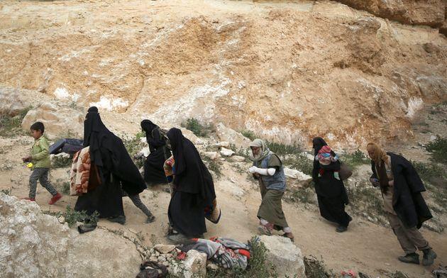 Des militants de Daech, des femmes et des enfants, marchent pendant qu'ils se rendent dans le village...
