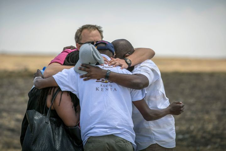 Family members and friends hug at the scene where the Ethiopian Airlines Boeing 737 Max 8 crashed shortly after takeoff on Su