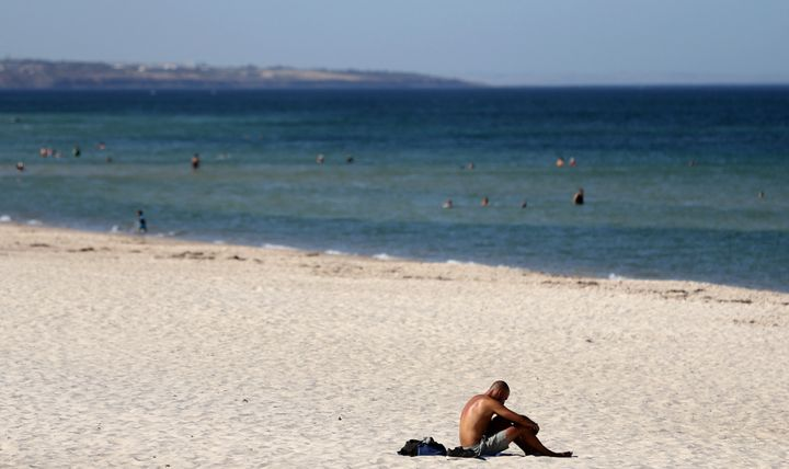 A beachgoer sits in the sun in Adelaide, Australia, in January, where temperatures reached a searing 115.9 degrees Fahrenheit