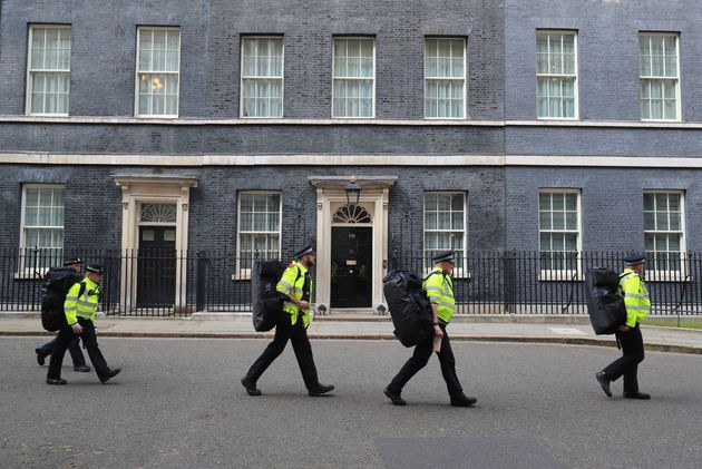 Police officers carry equipment through Downing Street in London, as multiple Brexit protests gathered...