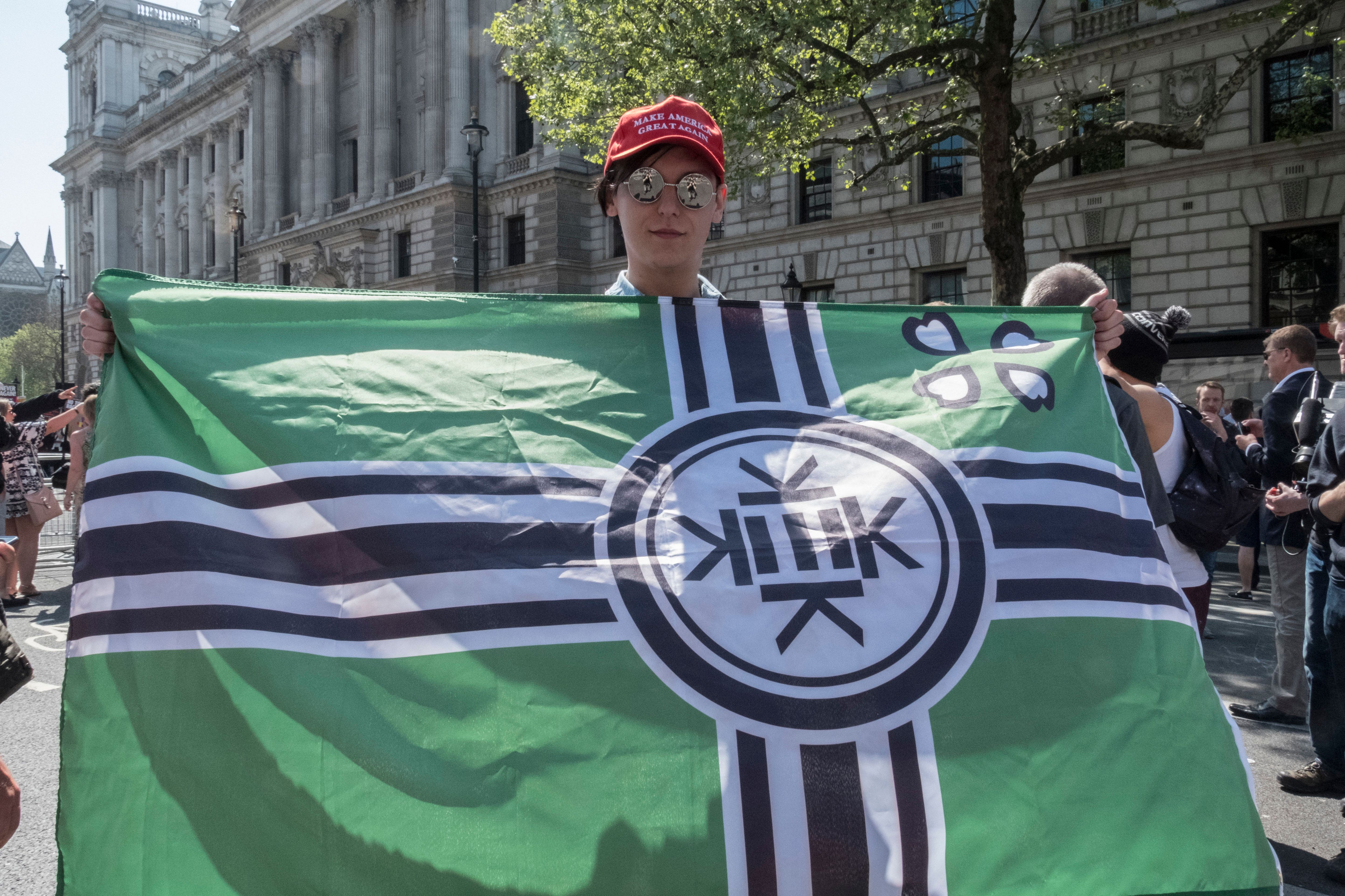 """A man at a Tommy Robinson rally in London holds an alt-right """"Kekistan"""" flag while wearing a Make America Great Again hat."""