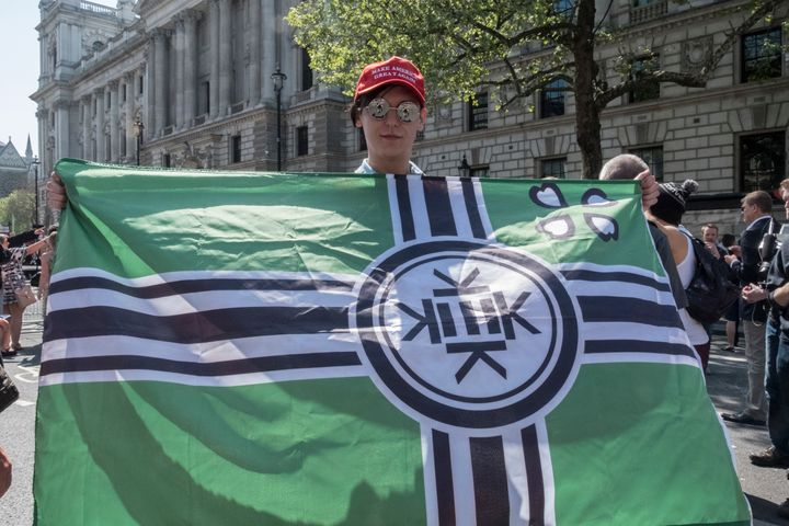"A man at a Tommy Robinson rally in London holds an alt-right ""Kekistan"" flag while wearing a Make America Great Again hat."