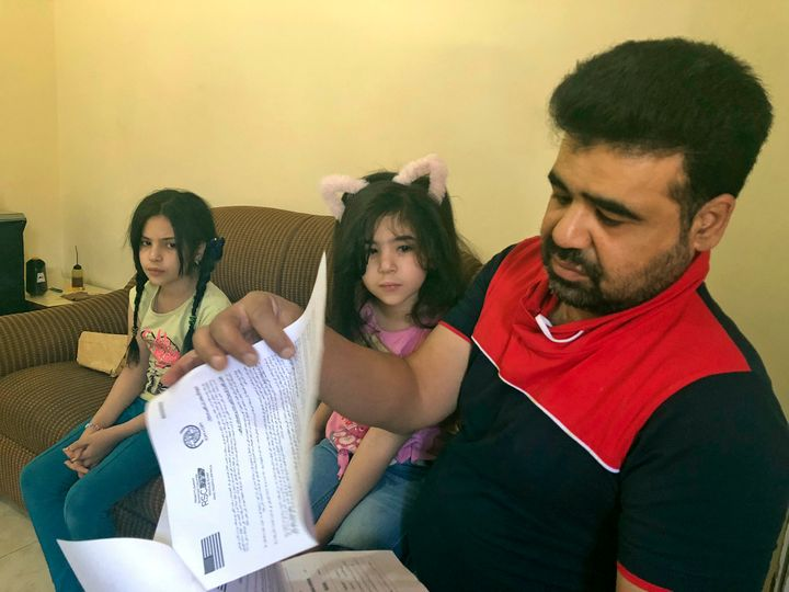 Syrian refugee Mahmoud Mansour, sitting with his daughters Sahar, 5, and Ruba, 11, holds documents for his U.S. resettlement
