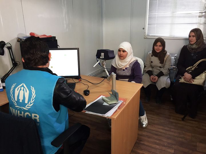 In this photo taken Sunday, Feb. 26, 2017, an 11-year-old Syrian refugee poses for a biometric iris scan in an interview room