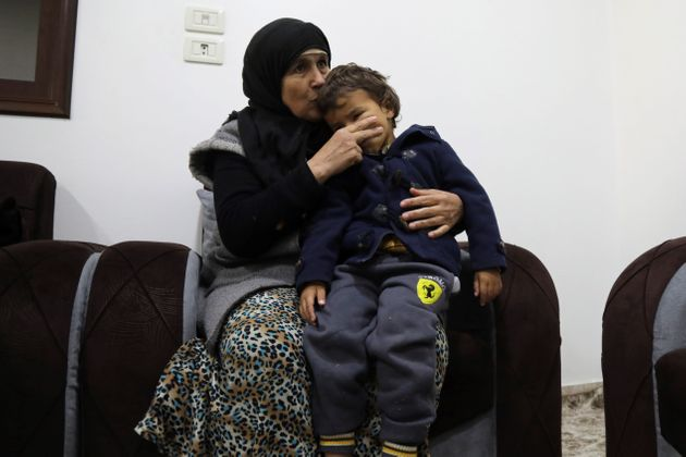 Latifa abraza a uno de sus nietos, en el lugar en que se encuentra atrapada, en