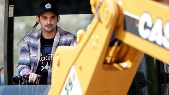Country music star Brad Paisley operates a backhoe as he breaks ground for The Store, a free grocery store for people in need, Wednesday, April 3, 2019, in Nashville, Tenn. (AP Photo/Mark Humphrey)