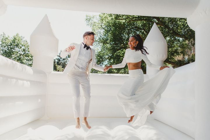 """Couple Tiffany and Victor <a href=""""https://torontolife.com/style/fashion/real-weddings-inside-white-affair-graydon-hall-bouncy-castle-costumed-hype-man/"""" target=""""_blank"""" rel=""""noopener noreferrer"""">had a bouncy castle</a> at their July 2017 wedding in Toronto.&nbsp;"""