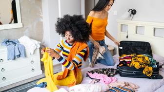Two girlfriends packing suitcases in hotel room.