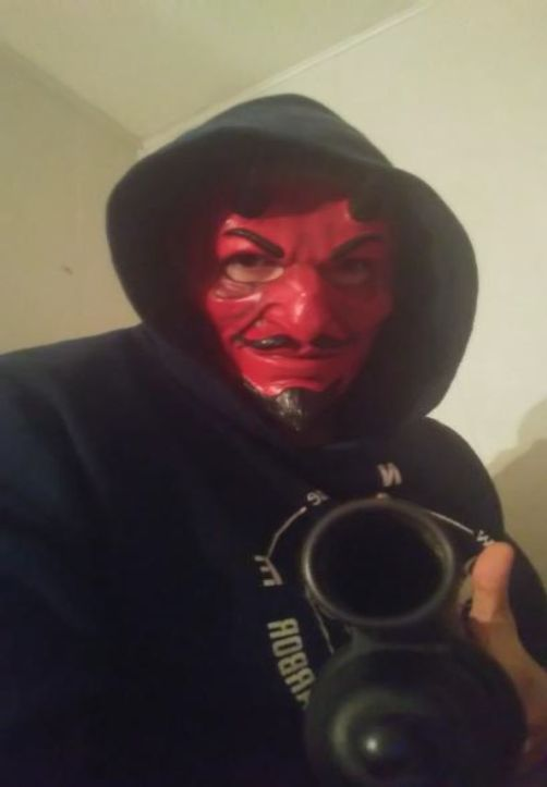 The feds say this photo depicts Thomas Alonzo Bolin wearing a red devil mask and holding a shotgun.