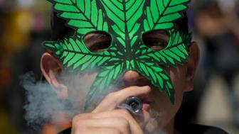 FILE - In this April 20, 2018, file photo, a young man smokes marijuana to celebrate the International Day for Cannabis in Mexico City. California became America's largest legal marketplace in 2018, while Canada became the second and largest country with nationwide legal recreational marijuana. And Mexico's Supreme Court set the stage for that country to follow, while governors in New York and New Jersey say they want broad legalization in their states next year. (AP Photo/Eduardo Verdugo, File)