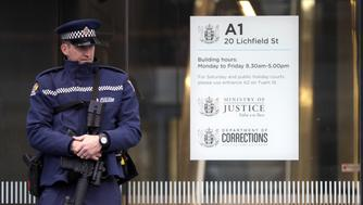 An armed police office stands guard outside the entrance to the High Court in Christchurch (Mark Baker/AP)