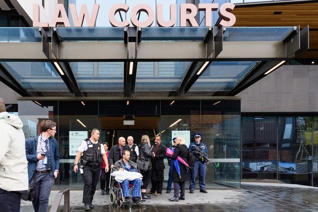 뉴질랜드 크라이스트처치 테러 생존자인 테멜 아타코쿠구(휠체어 탄 사람)가 법원을 나서고 있다. 이날 재판부는 언론의 법정 내 사진 및 영상 촬영을 일체 불허했으며, 오클랜드 보안 교도소에...