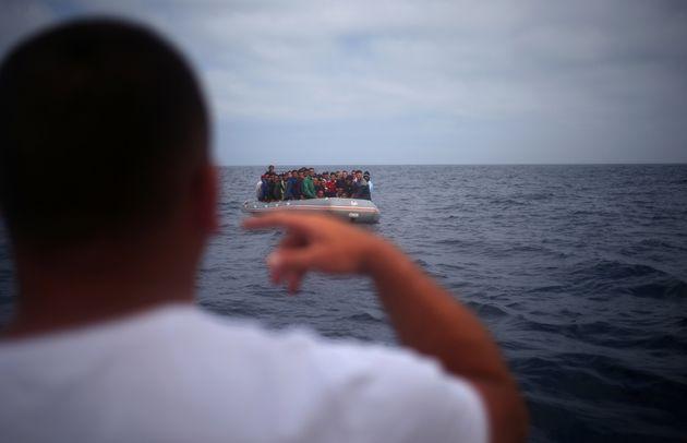 Un pêcheur s'entretient avec des migrants depuis un bateau avant de descendre d'un dériveur sur la plage