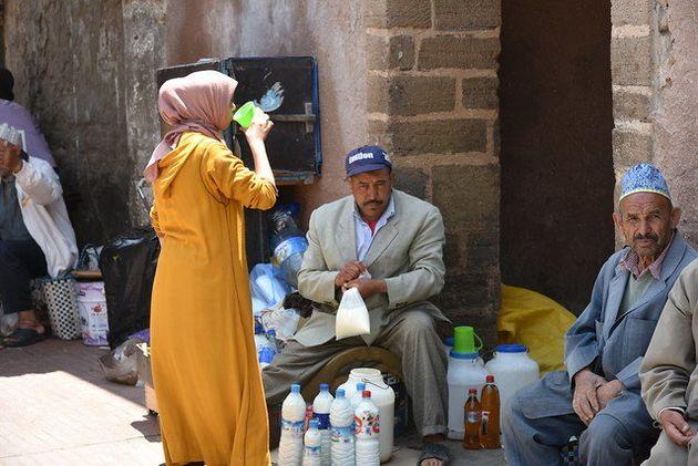 Une femme boit du lait frais vendu dans la médina d'Essaouira, mai