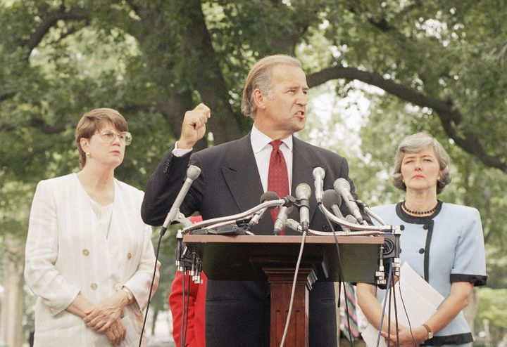 Sen. Joseph Biden (D-Del.), flanked by Attorney General Janet Reno, left, and Rep. Patricia Schroeder (D-Colo.), meets report
