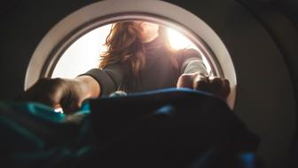 interior view of a washing machine with woman doing laundry