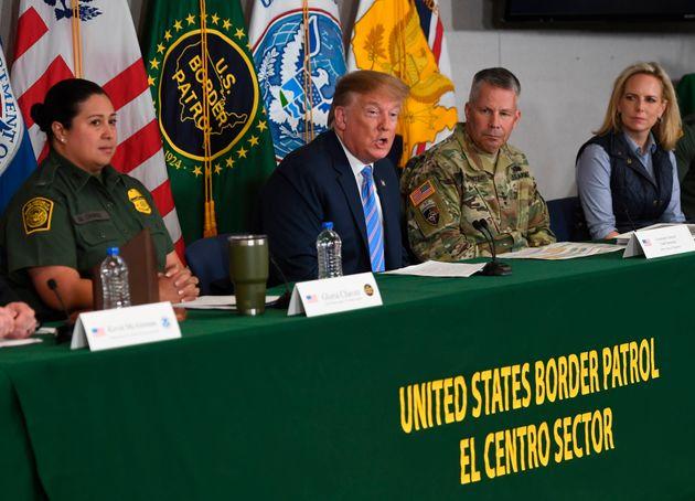 Trump speaks as Secretary of Homeland Security Kirstjen Nielsen (R) looks on during a roundtable on immigration...