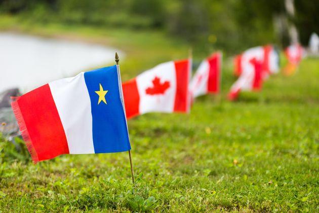 Un drapeau acadien et des drapeaux canadiens, photographiés dans la province canadienne du Nouveau