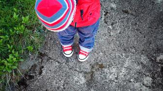 Funny cute boy looking onto own feet. Baby standing on saphalt in red shoes