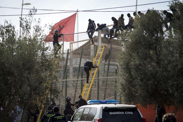 Des migrants africains s'installent au sommet d'une barrière frontalière lors d'une tentative...