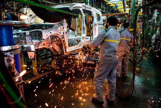 Des employés travaillent sur une chaîne de montage de voitures à l'usine d'assemblage...
