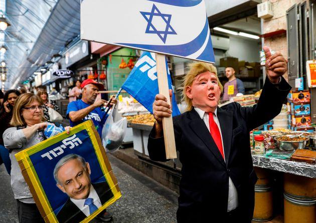 Un partisan du Premier ministre israélien Benjamin Netanyahou portant un masque sur le visage...