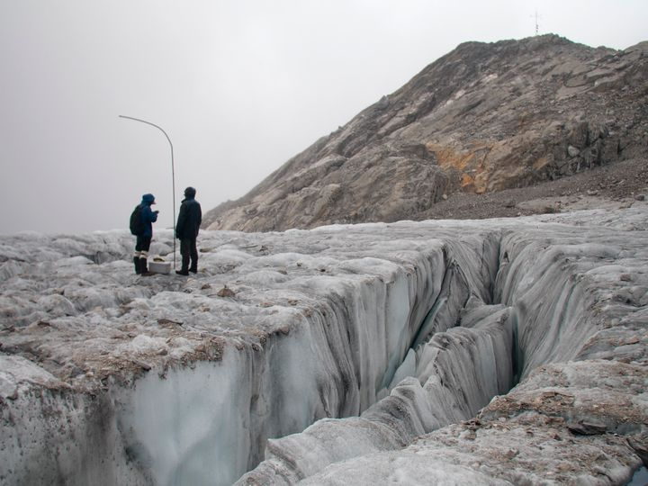 This Sept. 22, 2018 photo shows researchers measuring with iron bars the annual retreat of the Baishui Glacier No.1 on the Ja