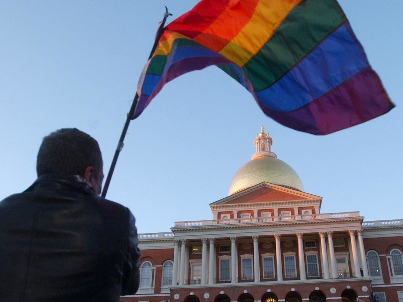 Demonstrator waves rainbow flag in front of Massachusetts Statehouse, Boston, photo