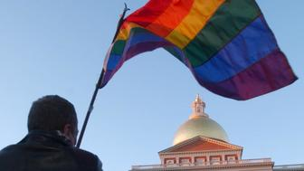 Demonstrator waves rainbow flag in front of Massachusetts Statehouse, Boston, photo