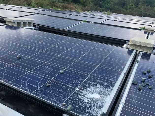 A shattered Tesla solar panel outside a water
