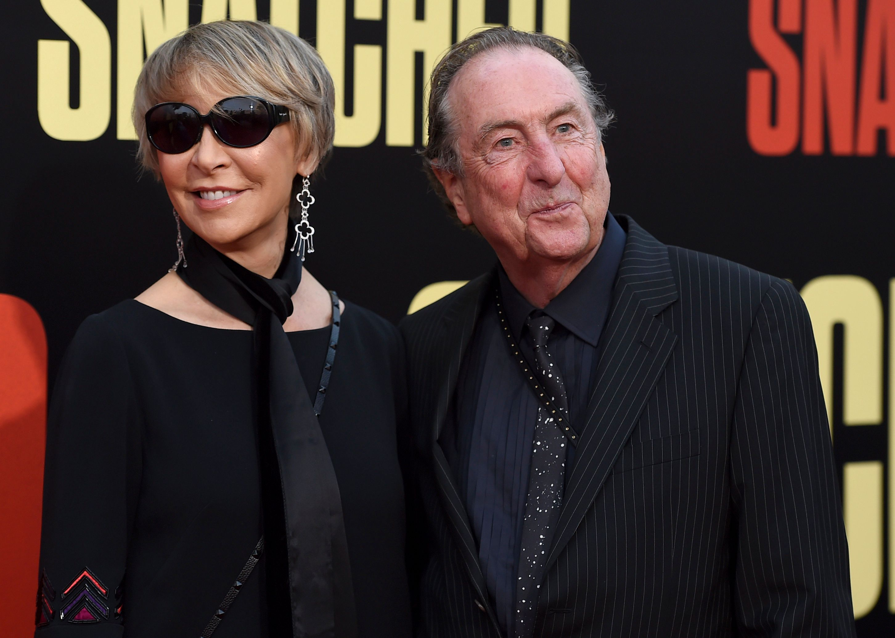 "Tania Kosevich, left, and Eric Idle arrive at the Los Angeles premiere of ""Snatched"" at the Regency Village Theater on Wednesday, May 10, 2017. (Photo by Jordan Strauss/Invision/AP)"