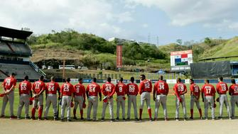 FILE - In this Feb. 10, 2019 file photo, Cuba's Los Leneros de las Tunas baseball players listen to their national anthem before facing Panama's Los Toros de Herrera for the final, Caribbean Series baseball tournament championship game at Rod Carew stadium in Panama City. The Trump administration is moving to end a deal allowing Cuban baseball players to sign contracts directly with Major League Baseball organizations, which appears to once again require Cuban players to cut ties with their national program before signing with MLB.  (AP Photo/Arnulfo Franco, File)