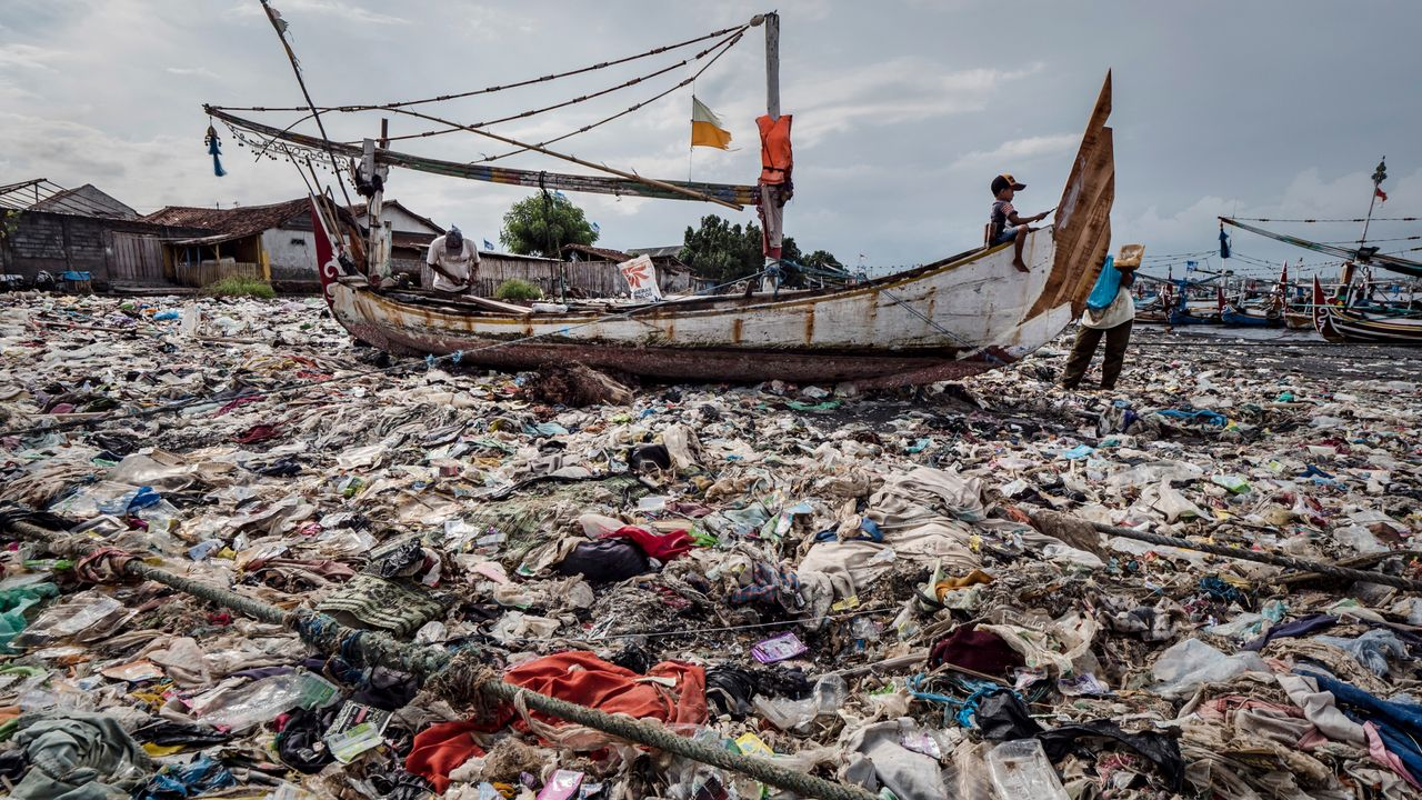 A boy paints a boat sitting on a beach smothered in plastic waste at Muncar port in Banyuwangi, East Java, Indonesia, on March 4, 2019.