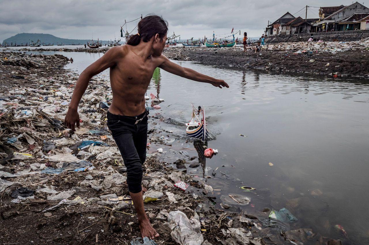Children playing amid plastic waste at Muncar port.