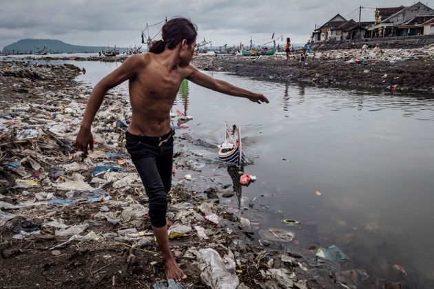 Children play at Muncar port in Indonesia. The city sits at the mouth of four rivers, into which communities...