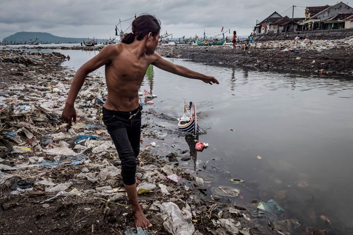 Children play at Muncar port in Indonesia. The city sits at the mouth of four rivers, into which communities toss their trash