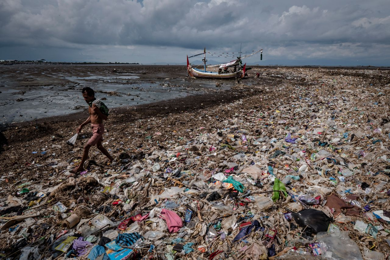 A man walks on a beach filled with plastic waste at Muncar port.