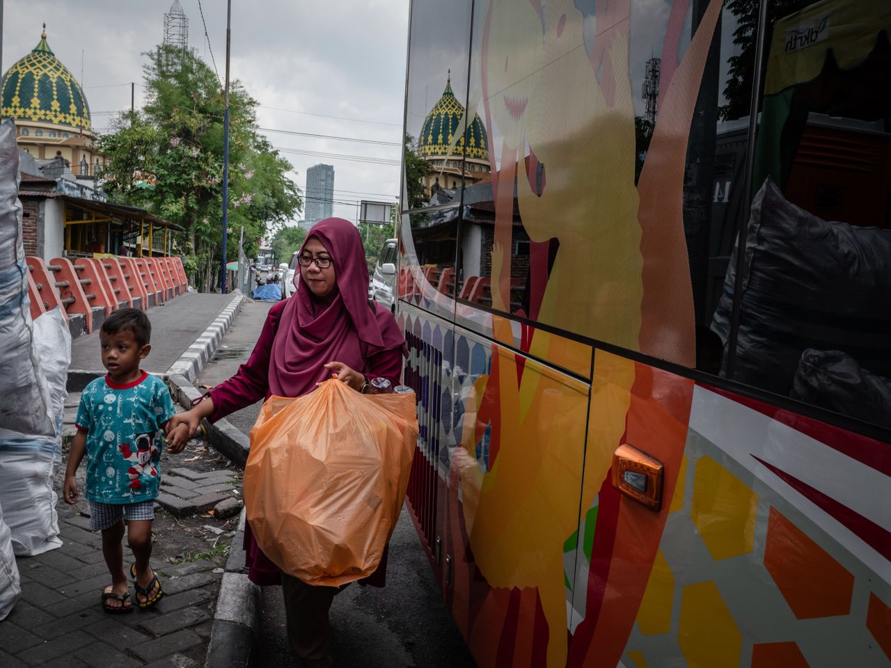 A woman brings used plastic bottles to exchange for bus tickets in Surabaya, East Java.