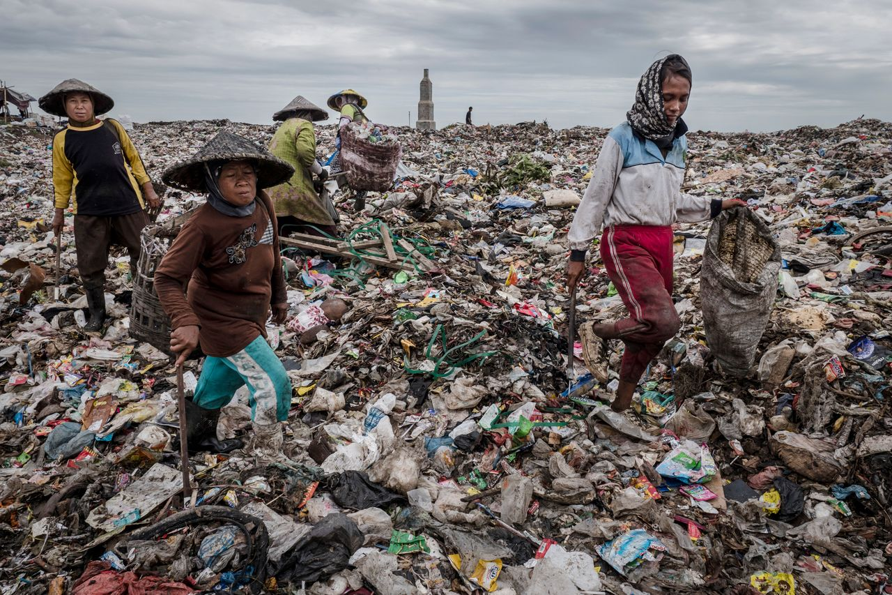 Waste pickers sift through a mountain of garbage at a landfill site near Sidoarjo.
