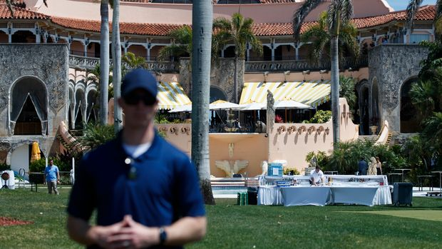 A member of the Secret Service is seen from the media van as he stands watch after President Donald Trump arrived at his Mar-a-Lago estate in Palm Beach, Fla., Sunday, March 25, 2018, as he returns from Trump International Gulf Club in West Palm Beach, Fla. A worker sets up a bar at poolside in the background. (AP Photo/Carolyn Kaster)