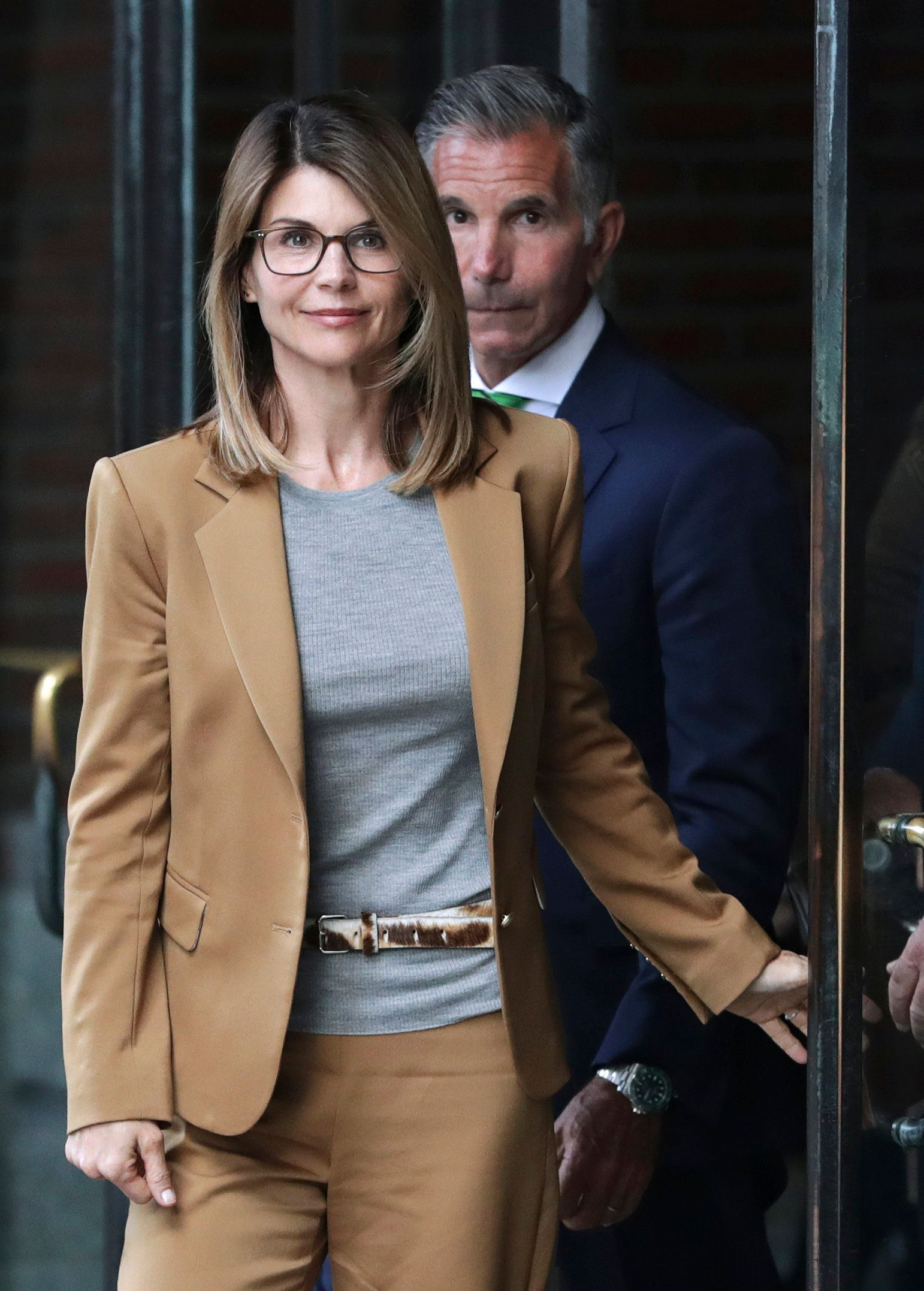 Actress Lori Loughlin, front, and husband, clothing designer Mossimo Giannulli, rear, depart federal court in Boston on Wednesday, April 3, 2019, after facing charges in a nationwide college admissions bribery scandal. (AP Photo/Charles Krupa)