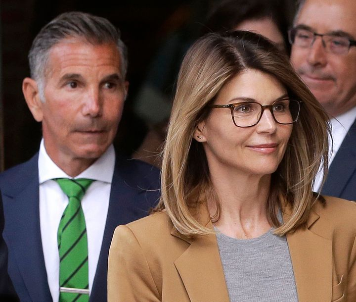 Actress Lori Loughlin, front, and her husband, clothing designer Mossimo Giannulli, left, depart federal court in Boston on A
